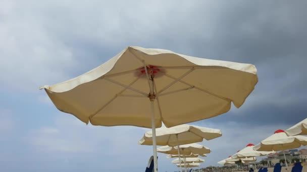 Sonnenschirm am Strand an einem windigen bewölkten Tag