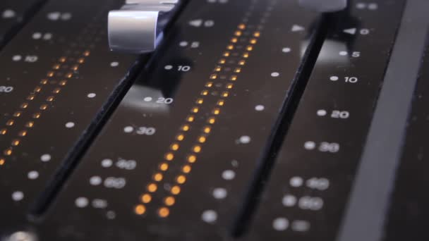Faders on a sound mixing desk in studio with audio levels