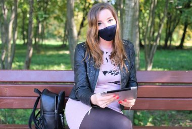A young girl wearing a protective mask sits on a bench during the COVID-19 pandemic and talks on the phone.
