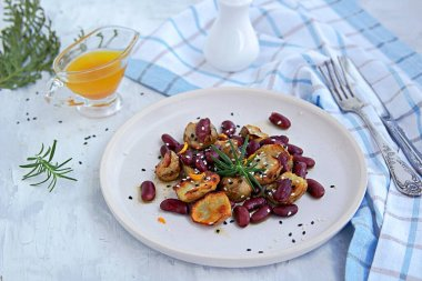 Warm salad of grilled Jerusalem artichoke and boiled red beans with olive oil and vinegar dressing on a white clay plate. Heathly food.