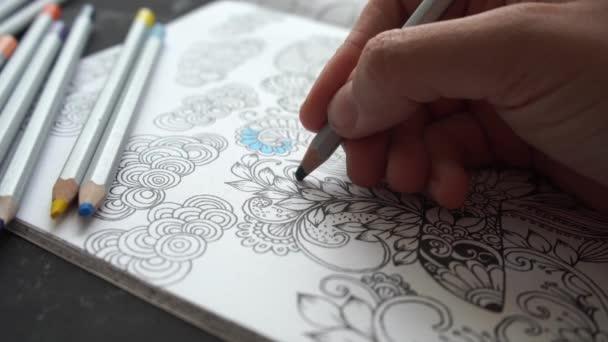 Osoba používá antistresovou omalovánku pro barevnou terapii umění. Kyjev, Ukrajina - květen 2020