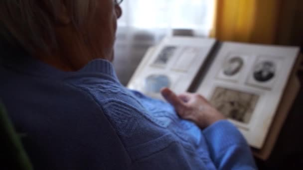 Starší žena sledující album se starými černobílými vinobranými fotografiemi