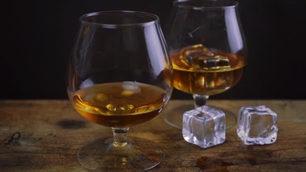 Eiswürfel im Cognac-Whiskey-Glas, goldene Farbe starker Spirituosenalkohol in Cognac-Gläsern auf dunkelschwarzem Hintergrund, Zeitlupe