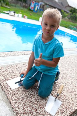 A little boy is working on a new pavement around the pool.