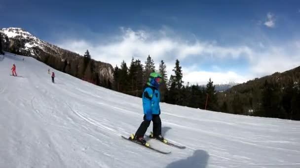 Malý chlapec lyžuje v alpském letovisku. Šest let staré dítě si užívá zimních svátků se svou matkou. Stabilizovaný záběr. Zpomaleně.