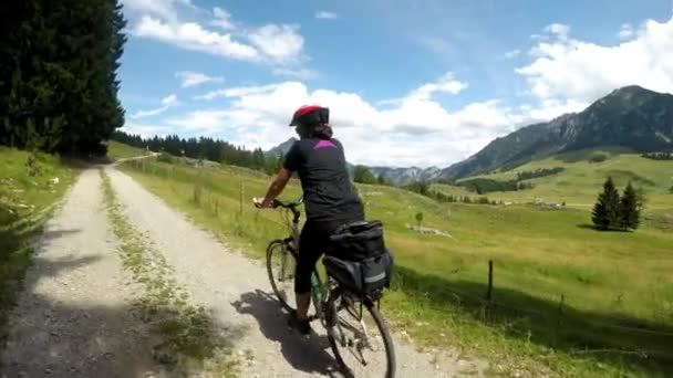 Letní čas v rakouských Alpách. Mladá žena na cyklistické cestě. Krásný cyklista se pohybuje krásnou krajinou. Rakouská dráha alpského cyklu. Stabilizované video.
