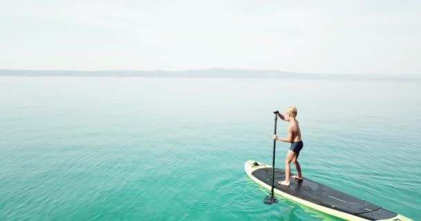 Sommerzeit am Meer. Luftaufnahme eines Kindes auf einem Paddelbrett. Niedliches Kind lernt auf einem Paddelbrett. Stabilisiertes 4K-Video.