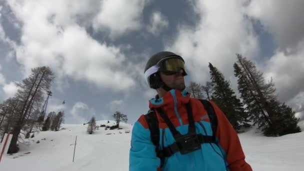 Junger Mann genießt das Skifahren. Ungewöhnliche Aufnahme von Skifahrern. Gefilmt von der Spitze des Skis. Stabilisiertes Material. Zeitlupe.