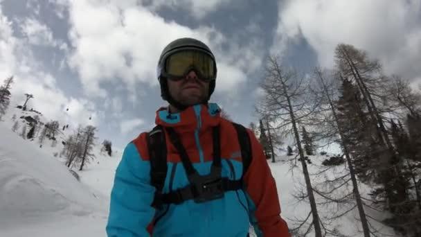 Mladý muž si užívá lyžování. Neobvyklý záběr na lyžaře. Natočeno ze špičky lyže. Stabilizované záběry. Zpomalený pohyb.