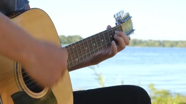 A man is playing guitar on the lake shore in summer.