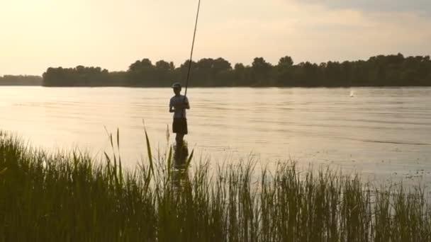 a fiú egy tinédzser Horgászbottal a folyó állandó és halászati.