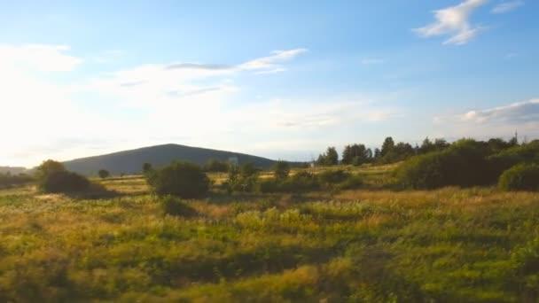 Pohled z okna vlaku. Vlak jede v létě večer