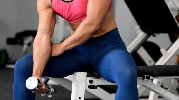 Žena sportovec trénuje biceps činky v posilovně.