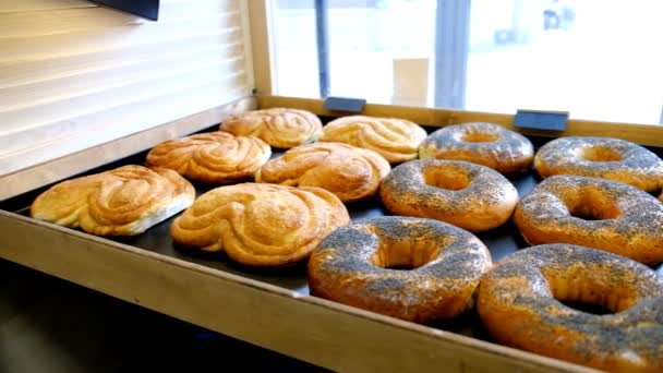the pastry chef lays out fresh pastries on the storefront in the bakery.