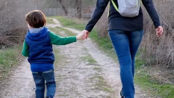 Žena se svým malým synem chodí na jaře v parku