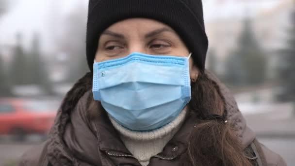 Eine junge Frau in medizinischer Maske steht am Straßenrand in der Stadt. Schutz vor Grippeviren.