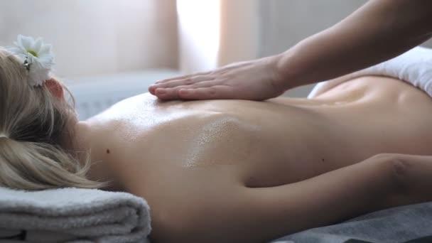 Ein Masseur macht einer jungen Frau eine professionelle Rückenmassage.