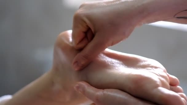 Professional massage therapist does a foot massage to a young woman.