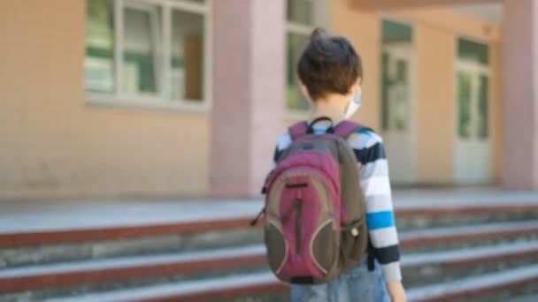 Egy fiú orvosi maszkban iskolába megy és integet a kezével. A COVID-19 koronavírus járvány után egy hátizsákos fiú újra iskolába jár..