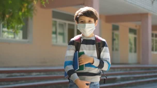 Az anya elkíséri a fiát az iskolába, és elbúcsúzik tőle. Egy iskolás fiú védőmaszkban iskolába jár..