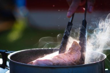Close up Chef hand with Tongs holding meat steak frying on iron cast with smoke and oil splash blurred background