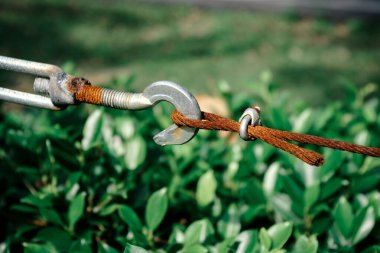 detail of rusty sling and hook in garden