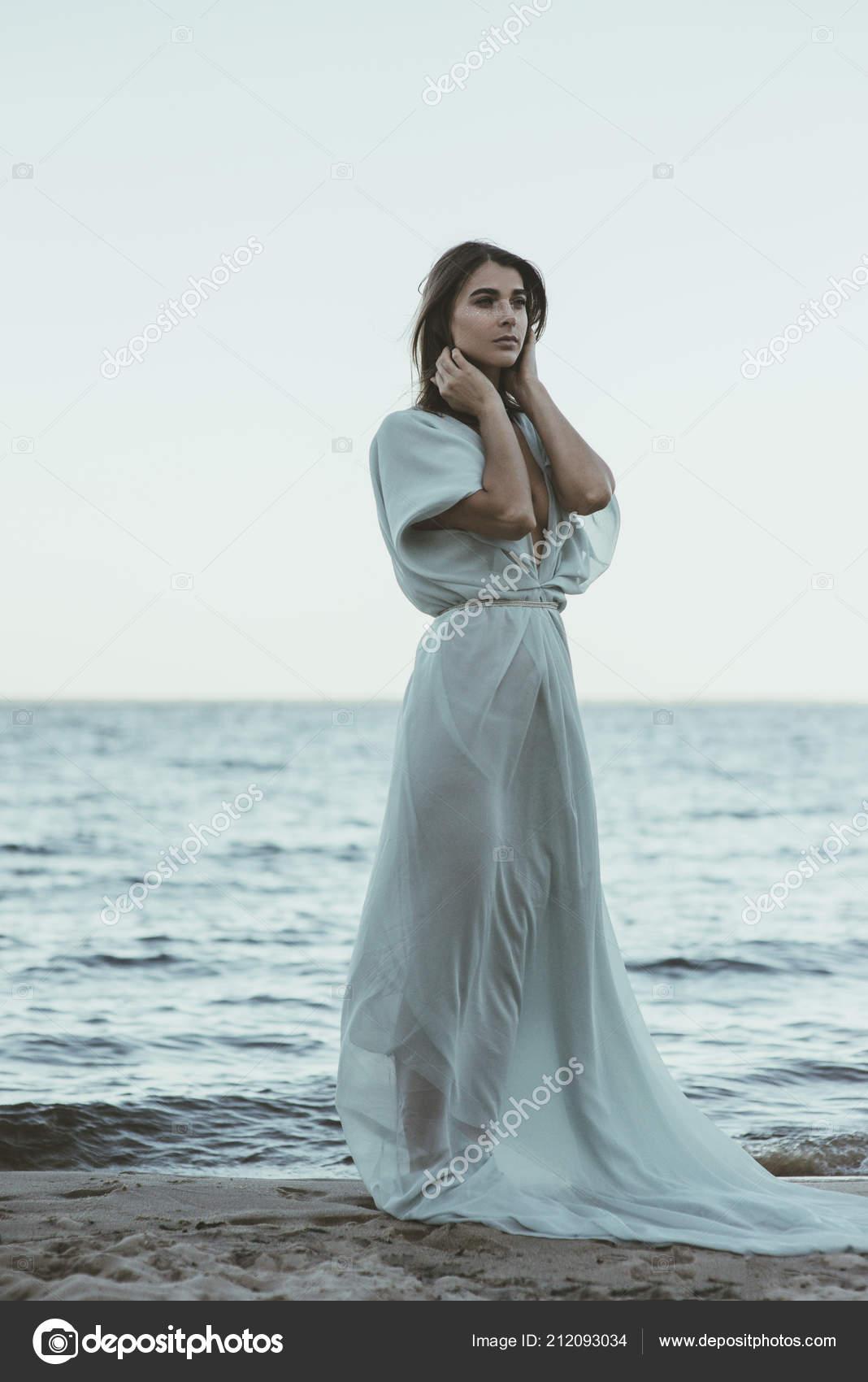 5f40928f0d4b Όμορφη και αισθησιακή νεαρή γυναίκα με μεγάλο λευκό ροή φόρεμα στέκεται  στην παραλία — Εικόνα από ...