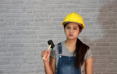 Technician woman ware yellow helmet with grey T-shirt and denim jeans apron dress standing and rubber hammer in hand on grey brick pattern background.