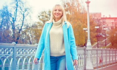 Attractive middle aged woman in blue coat walking in the city. Plus size Fashion woman portrait of trendy lady posing at the city in Europe street fashion