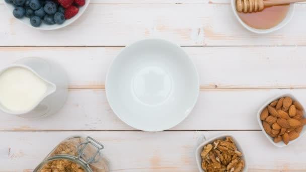 Müsli mit Naturjoghurt, frische Heidelbeeren, Nüssen und Honig, leckeres Frühstück oder Dessert, Ansicht von oben. Gesunde Ernährung-Konzept.