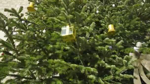 Vánoční stromeček s stříbro luky, zlatými ornamenty mimo na pozadí historického zdi.