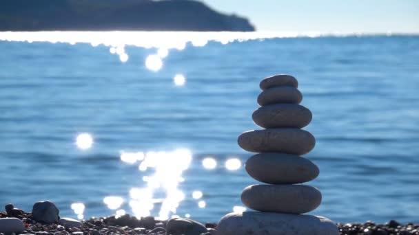 Zen Stones on beach for perfect meditation. Calm zen meditate background with rock pyramid on sand beach symbolizing stability, harmony, balance.