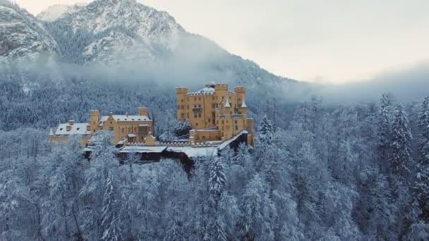 Luftaufnahme des Schlosses Hohenschwangau bei Sonnenaufgang in winterlicher Landschaft.