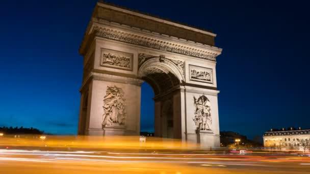 Oblouk de Triomph v Paříži v noci. Tento historický památník má výhled na bulváj, který se nachází v samém srdci francouzského hlavního města.