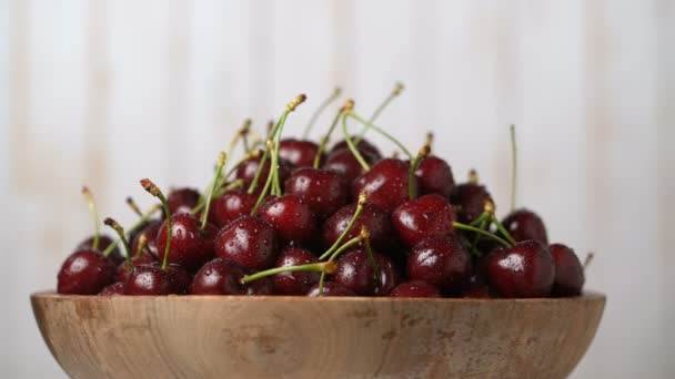Fresh, ripe, juicy cherries in a wooden bowl, rotation loopable. Food background. Gastronomy concept, organic food.