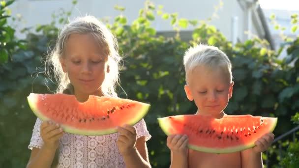 Bruder und Schwester essen Wassermelone im Garten