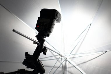 Camera flash flashes in a white umbrella in the photography studio.
