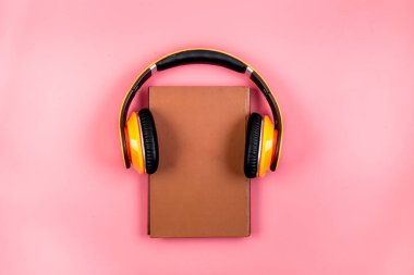Book and yellow headphones on. Pink background top view
