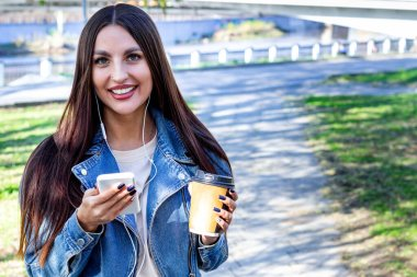 portrait of smiling young woman with smart phone and coffee outdoor