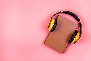 Book and yellow headphones on. Pink background top view copy space