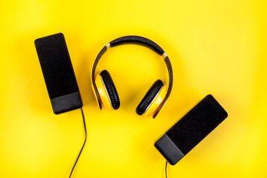 headphones and black speakers on yellow table top-down