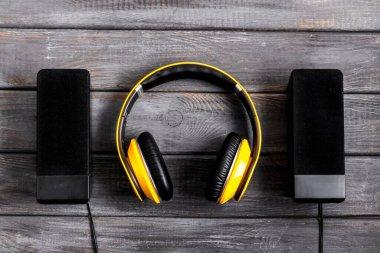 headphones and black speakers on wooden table top-down