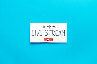 Live streaming concept - words on paper tablet on blue top view