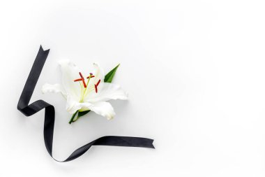 Funeral concept with lily and black ribbon, space for text