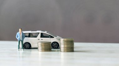 A car with a miniature man standing next to a pile of coins.