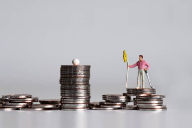 A miniature golfer standing with a golf club and flag on a pile of coins.