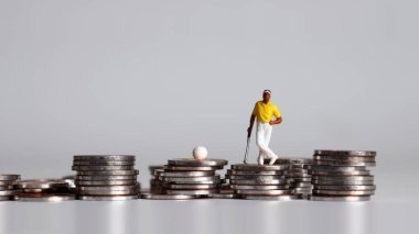 Miniature golfer standing on a pile of coins.