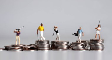 Miniature golfers standing on pile of coins.