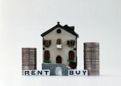 Der weiße Würfel aus KAUFEN und RENT Text mit einem Miniaturhaus. Ein Miniaturhaus und Münzen stapeln sich.
