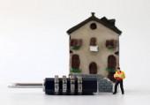 Ein Miniatur-Kurier mit Schloss vor einem Miniaturhaus.